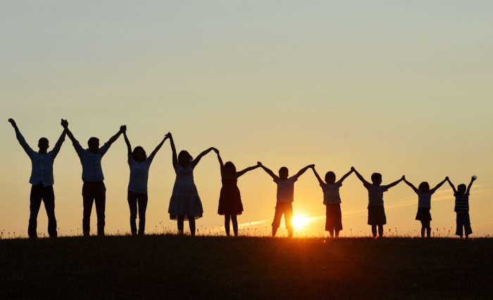 Group of people with hands held high before a sunset